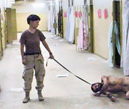 Pvt. Lynndie England and a prisoner at Abu Ghraib