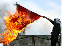 A Palestinian burns a Danish flag in Bethlehem. Click image to expand.